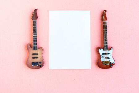 Toy bass and electric guitars and white mockup blank on pink background, top view, copy space for the text Stockfoto