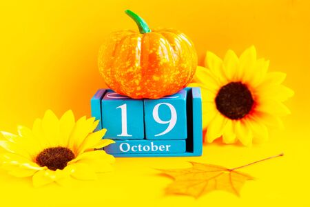 October 19th. Wooden cube calendar with month and date on bright orange background
