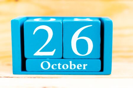 October 26. Blue cube calendar with month and date on wooden background.