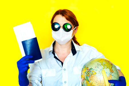 Portrait of a girl in medical mask and sunglasses with documents and globe in her hands
