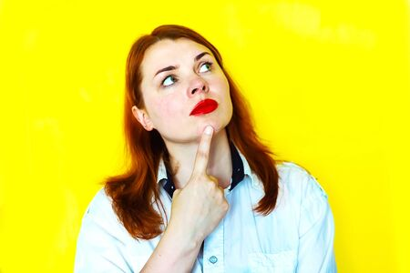 Portrait of thoughtful redhead girl on yellow background