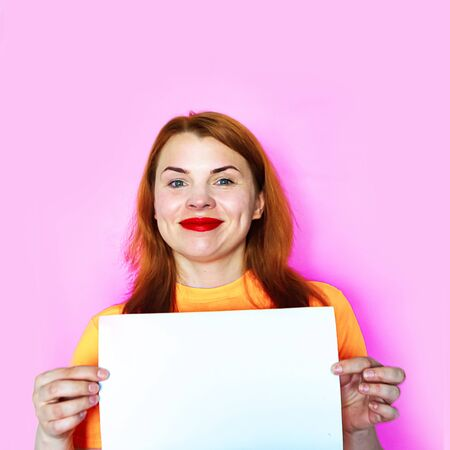 Redhead girl is holding white mockup blank on pink background