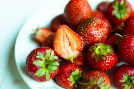Fresh tasty strawberry on white plate, top view