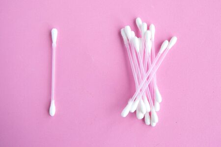 Cotton buds on pink pastel background, top view