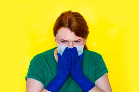 Redhead girl in medical gloves is sneezing in her hands