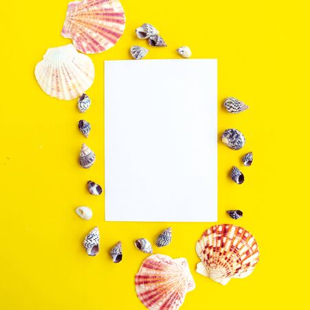 White mockup blank and seashells on yellow background, top view. Summer vacation concept