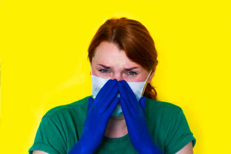Redhead girl in medical gloves is sneezing in her hands, covid-19 concept 版權商用圖片