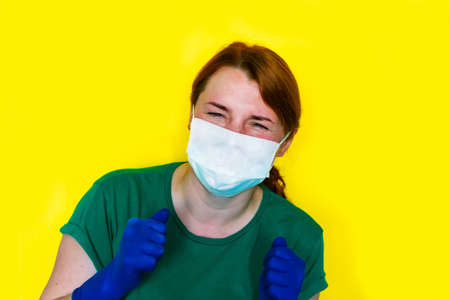 Redhead girl in medical gloves is sneezing on yellow background, covid-19 concept