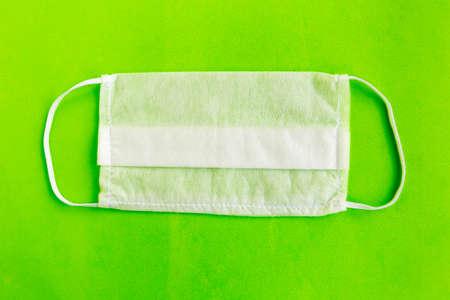 Medical mask on green background, covid-19 concept Foto de archivo - 151335298