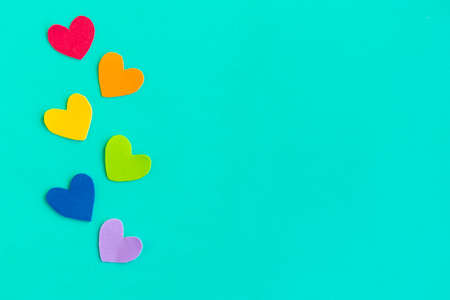Hearts in lgbtq colors on green background, top view, copy space