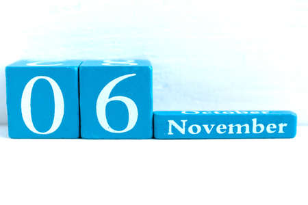 November 6. Blue cube calendar with month and date on wooden background. Banco de Imagens