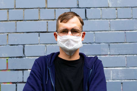 Portrait of a guy in a protective mask on a brick background. Image of a young man's face in a mask to prevent germs.