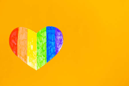 Heart in lgbtq colors on bright orange background, top view, copy space
