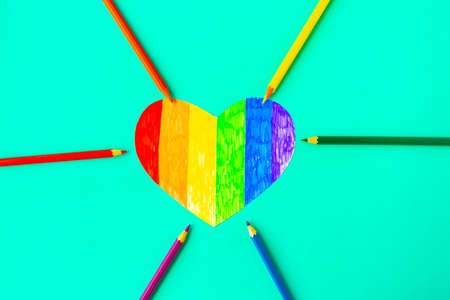 Heart in lgbtq colors and pencils on green mint background, top view Banque d'images