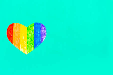 Heart in lgbtq colors on green mint background, top view, copy space