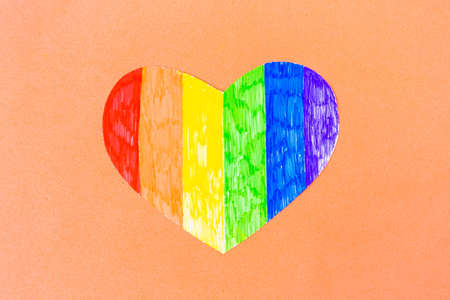Heart in lgbtq colors on pastel pink background, top view