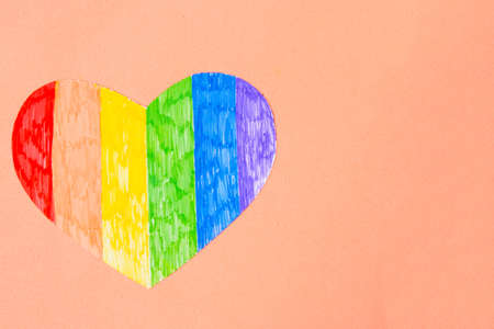 Heart in lgbtq colors on pastel pink background, top view, copy space