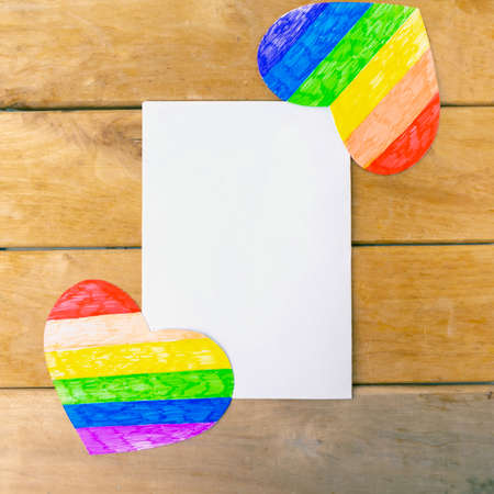 Two hearts in lgbtq colrs and white mockup blank on wooden background, top view