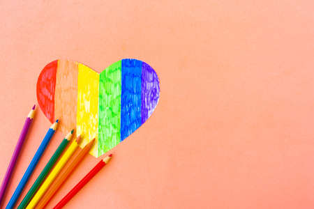 Heart in lgbtq colors and pencils on pastel pink background, top view, copy space