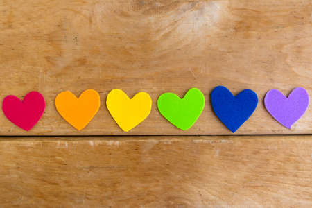 Hearts in lgbtq colors on wooden background, top view