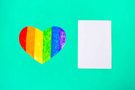 Heart in lgbtq colors and white mockup blank on green mint background, top view, copy space Banque d'images