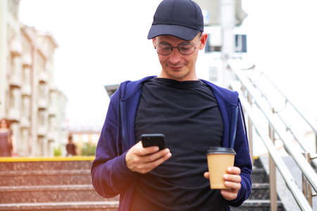 Young man goes down to the underpass and holding takeaway coffee and phone Stock Photo