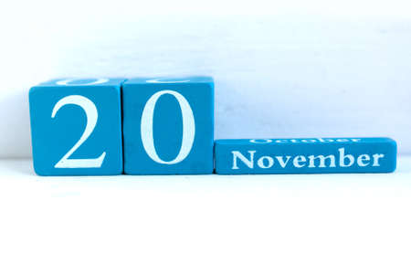 November 20. Blue cube calendar with month and date on wooden background.