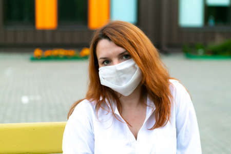 Portrait of redhead girl in medical mask, closeup