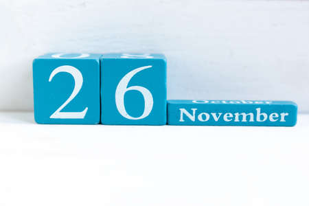 November 26. Blue cube calendar with month and date on wooden background.