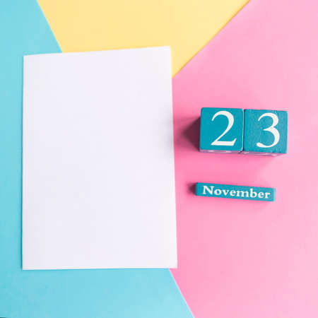 November 23. Blue cube calendar with month and date on color geometric background.
