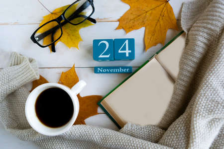 November 24.Blue cube calendar with month and date on wooden background.