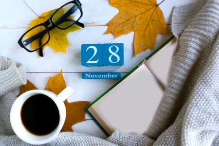 November 28. Blue cube calendar with month and date on wooden background. Zdjęcie Seryjne