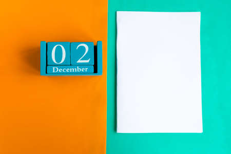 December 2. Blue cube calendar with month and date and white mockup blank on color background. Zdjęcie Seryjne