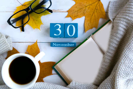 November 30.Blue cube calendar with month and date on wooden background.
