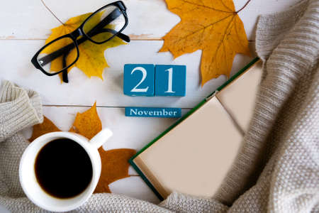 November 21.Blue cube calendar with month and date on wooden background. Zdjęcie Seryjne