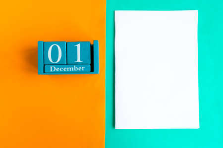 December 1. Blue cube calendar with month and date and white mockup blank on color background. Zdjęcie Seryjne