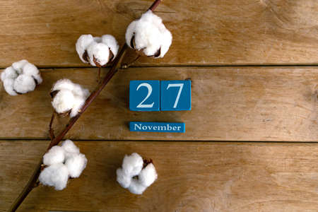 November 27. Blue cube calendar with month and date on wooden background. Zdjęcie Seryjne