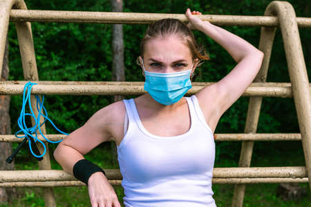 Woman wearing surgical mask doing training in the forest, coronavirus concept