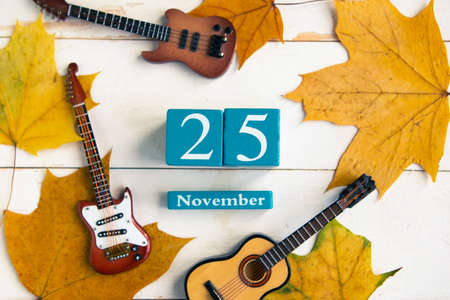 November 25.Blue cube calendar with month and date on wooden background.