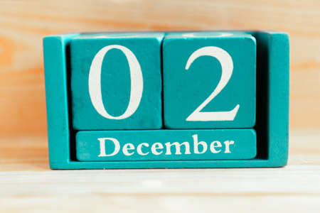 December 2. Blue cube calendar with month and date on wooden background. Zdjęcie Seryjne