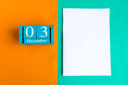 December 3. Blue cube calendar with month and date and white mockup blank on color background.