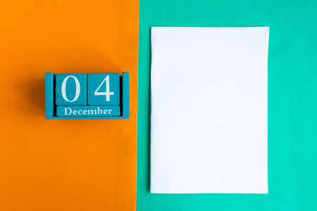December 4. Blue cube calendar with month and date and white mockup blank on color background.