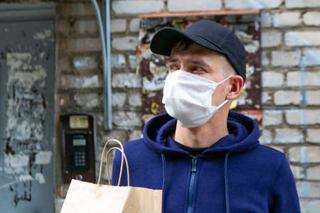 Courier in protective mask delivers takeaway food. Coronavirus covid-19 pandemic conditions. 免版税图像