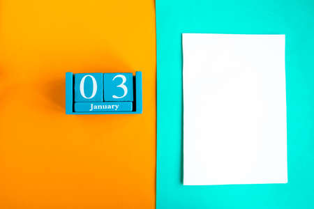 January 3. Blue cube calendar with month and date and white mockup blank on color background.
