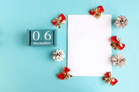 December 6. Blue cube calendar with month and date and white mockup blank on blue background.