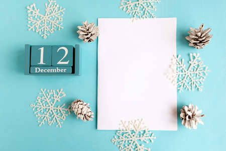 December 12. Blue cube calendar with month and date and white mockup blank on blue background.
