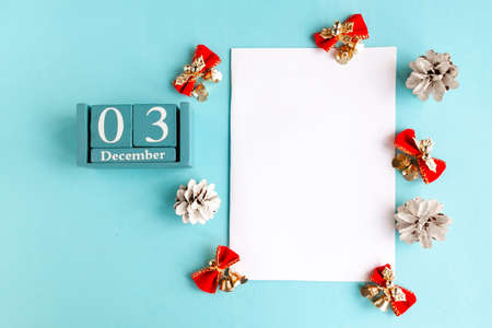 December 3. Blue cube calendar with month and date and white mockup blank on blue background.