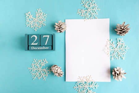 December 27. Blue cube calendar with month and date and white mockup blank on blue background.
