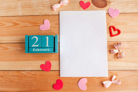 February 21. Blue cube calendar with month and date and white mockup blank on wooden background.