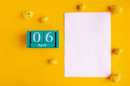 April 6. Blue cube calendar with month date and white mockup blank on yellow background.